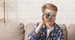 Boy Holding Doughnut Near Eye Posing Sitting On Couch, Panorama