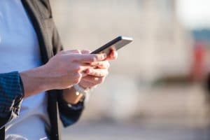 Closeup of male hands is holding cellphone outdoors on the street. Man using mobile smartphone
